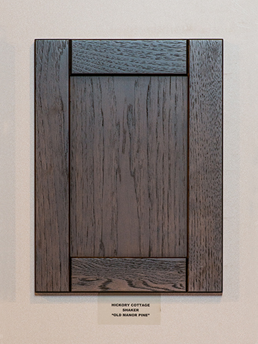A hickory kitchen cabinet door, in the Old Manor Pine finish